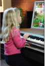 Child playing a piano purchased from Hollywood Piano Company