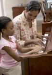 A mother and child playing a piano purchased from Hollywood Piano Company